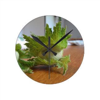 Relógio Redondo Avelã verdes frescas em uma mesa de madeira