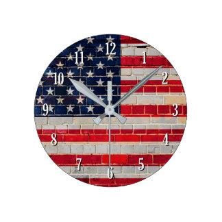 Relógio Redondo Bandeira de América em uma parede de tijolo