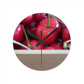 Relógio Redondo Beira de cerejas frescas no fundo de madeira