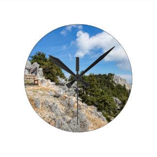 Relógio Redondo Bench na montanha rochosa com árvores e o céu azul