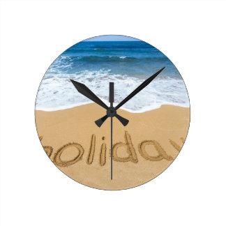 Relógio Redondo Feriado da palavra escrito na areia na praia