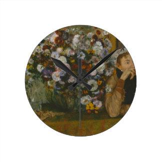Relógio Redondo Uma mulher assentada ao lado de um vaso das flores