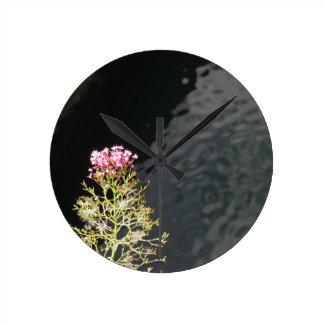Relógio Redondo Wildflowers contra a superfície da água de um rio