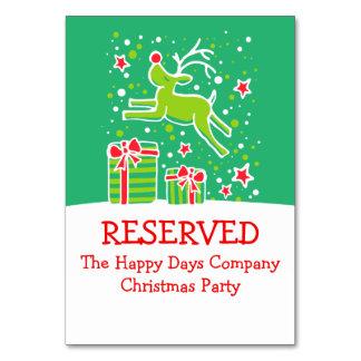 Rena do Natal que salta o cartão reservado da mesa