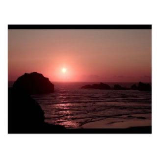 Rocha da cara no por do sol no cartão de Bandon