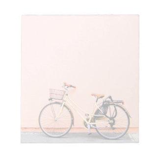 Roda cor-de-rosa da bicicleta dois da cesta da bloco de anotação