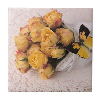 rosas amarelos com azulejo da borboleta