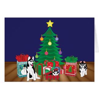 Roucos que jogam sob o cartão da árvore de Natal