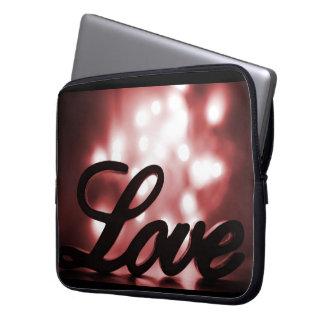 Sinal do amor com luzes vermelhas da faísca atrás bolsa e capa para computadore