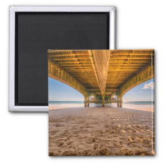 Sob um cais, praia, areia, pegadas, céu azul ímã quadrado