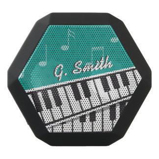 Teclado de piano preto e branco feito sob caixa de som preta com bluetooth
