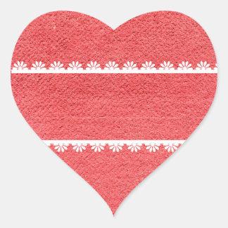 Textura vermelha do tecido com laço branco adesivo coração