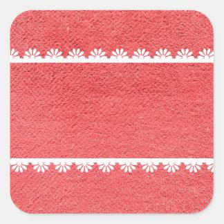 Textura vermelha do tecido com laço branco adesivo quadrado