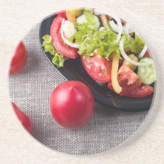 Tomates frescos e uma peça de uma placa porta copos de arenito