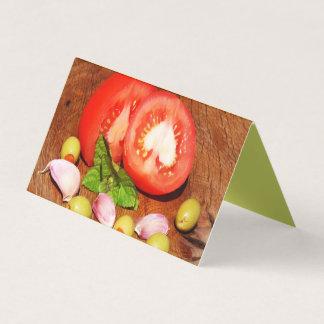Tomates no cartão de visita de madeira