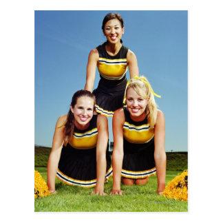 Três cheerleaderes que formam a pirâmide humana cartão postal
