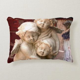 Três querubins em uma fonte almofada decorativa
