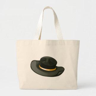 Um chapéu negro com uma correia amarela bolsa para compra