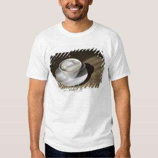 Um copo do café do cappuccino encontra-se em um t-shirts