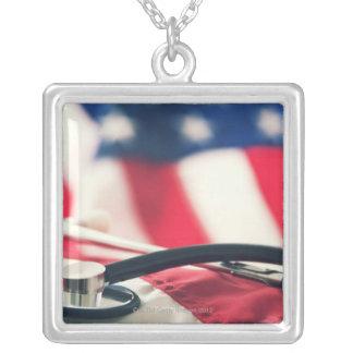 Um estetoscópio médico com uma bandeira americana colar com pendente quadrado