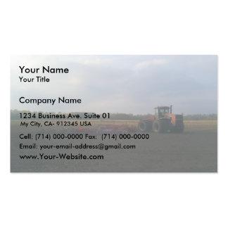 Um trator vermelho que descansa nos campos abertos cartoes de visita