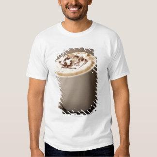 Uma caneca de café do Cappuccino cobriu com T-shirt