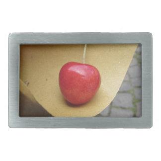 Uma cereja vermelha no papel da comida da palha