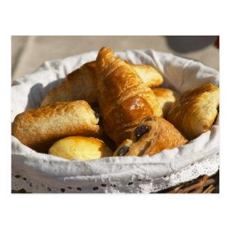 Uma cesta de vime do pequeno almoço com croissants cartao postal