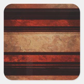 Uma listra preta e vermelho em um fundo de madeira adesivo quadrado