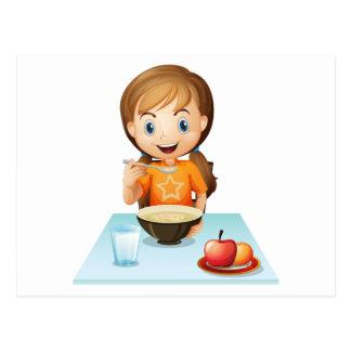 Uma menina de sorriso que come seu pequeno almoço cartões postais