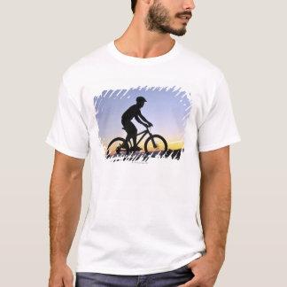 Uma silhueta de um motociclista da montanha no por camiseta