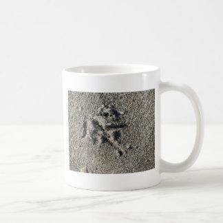 Única pegada do pássaro da gaivota na areia da caneca de café