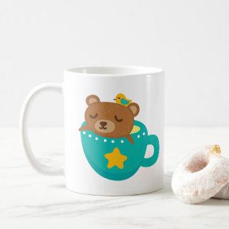 Urso de ursinho bonito que dorme na caneca da