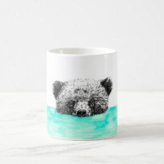Urso de urso que banha-se na caneca de café da
