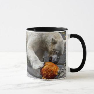 Urso polar que come uma abóbora caneca