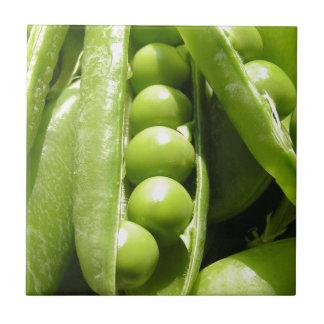 Vagens de ervilha verde abertos frescos na luz