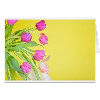 Vista às tulipas coloridos sobre o papel amarelo cartão