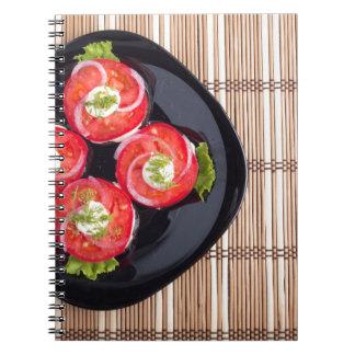 Vista superior de um prato com os tomates cortados cadernos espiral