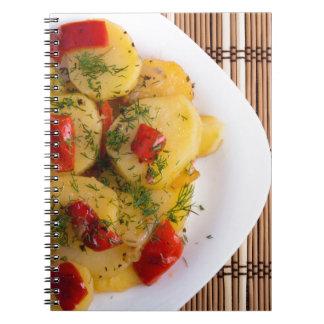 Vista superior de um prato de vegetariano com caderno espiral
